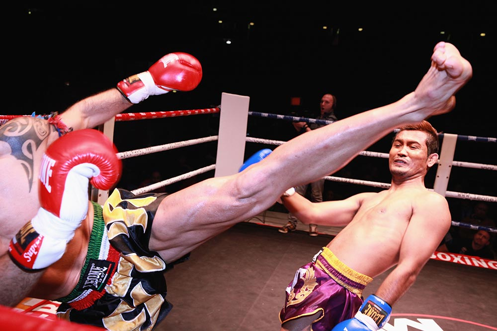 Professional Muay Thai fighter avoids a high kick.