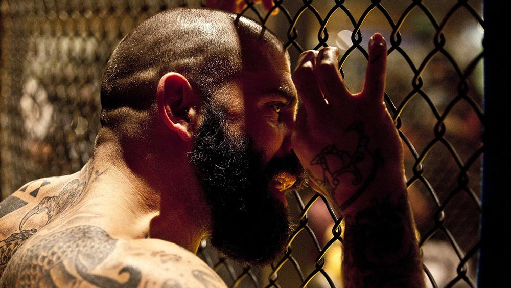 MMA fighter looking through the cage wire.