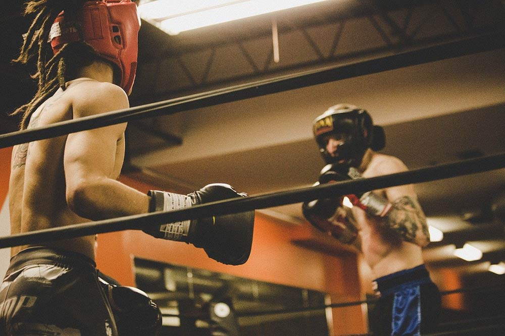 Two fighters MMA sparring in a boxing ring.