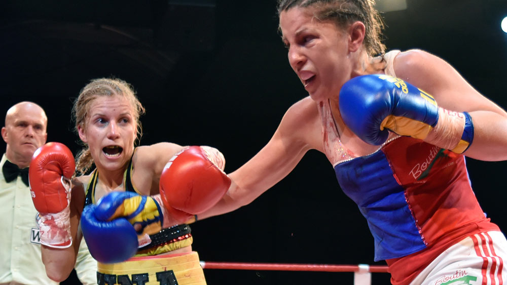 Two female boxers exchange punches in the boxing ring.