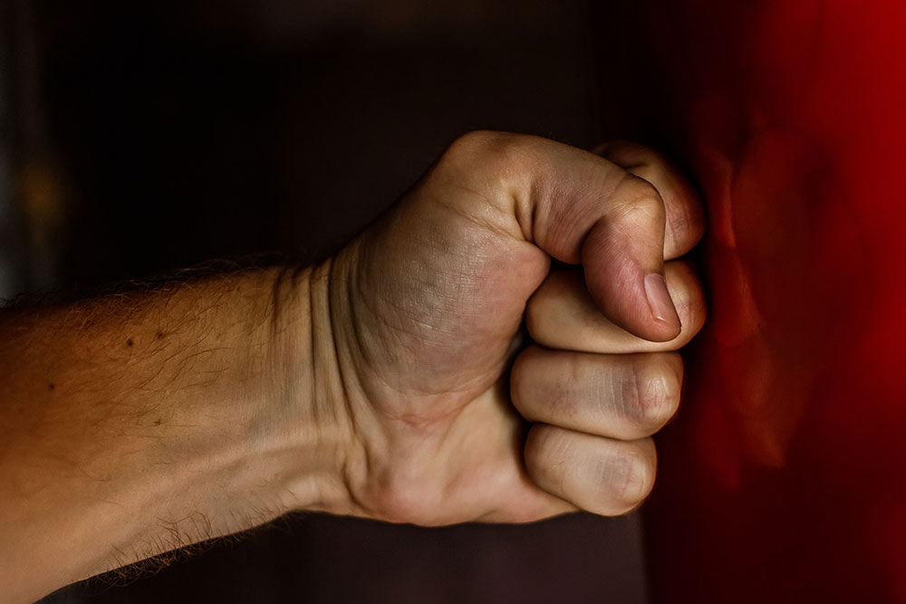A fist punching a red boxing heavy bag.