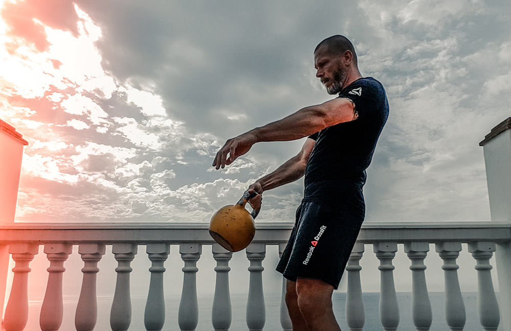 Man training with a kettlebelll for mma conditioning.