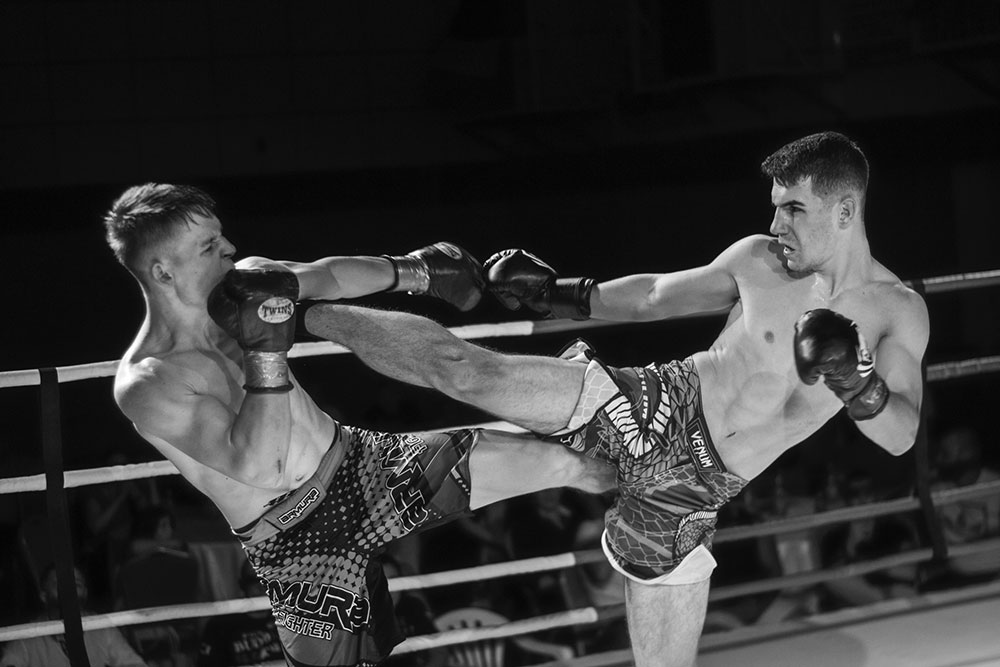 Two men kickboxing in the ring.