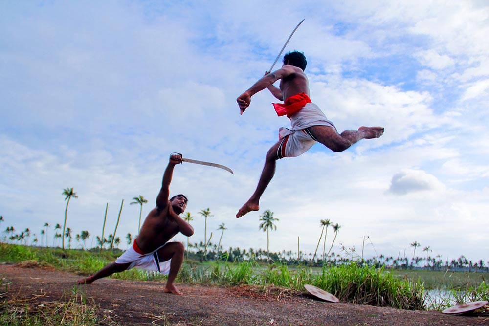 Two men sword fighting outdoors wearing while shorts.