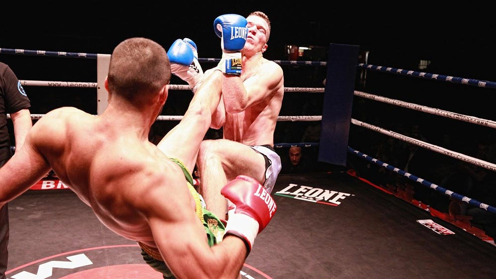 One kickboxer kicking his opponent in the face.