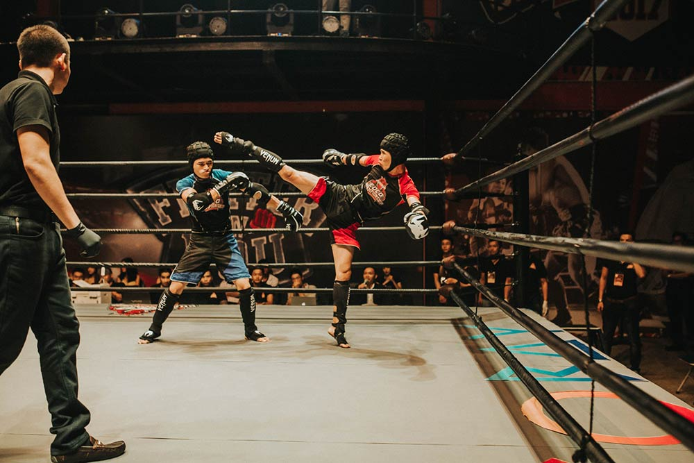 Two kickboxers with padding competing inside the ring.