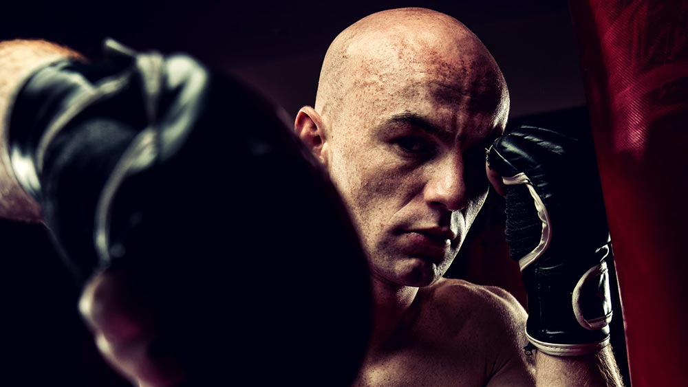 An mma fighter punches toward the camera during training.